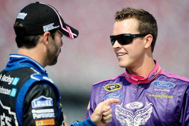 Jimmie Johnson, driver of the #48 Lowe's Chevrolet, talks with Trevor Bayne, driver of the #21 Motorcraft/Quick Lane/Warriors in Pink Ford, on the grid during qualifying at Talladega fall race 2012