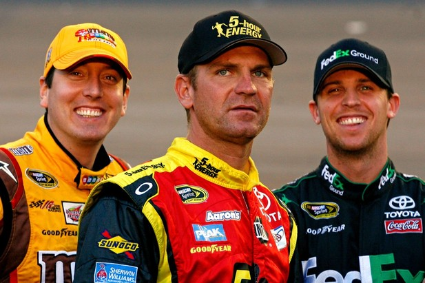 AVONDALE, AZ - NOVEMBER 09: Kyle Busch (L), driver of the #18 M&M's Toyota, Denny Hamlin (R), driver of the #11 FedEx Ground Toyota, and Clint Bowyer (C), driver of the #15 5-hour Energy Toyota, joke on the grid during qualifying for the NAS