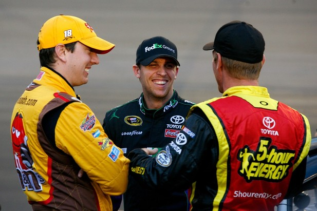 AVONDALE, AZ - NOVEMBER 09: (L-R) Kyle Busch, driver of the #18 M&M's Toyota, talks with Denny Hamlin, driver of the #11 FedEx Ground Toyota, and Clint Bowyer, driver of the #15 5-hour Energy Toyota, on the grid during qualifying for the NAS