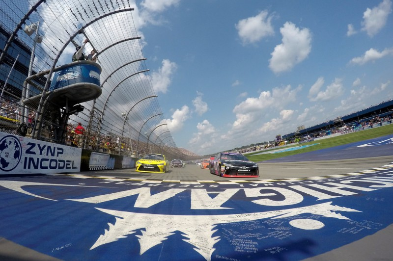 Matt Kenseth, driver of the #20 Dollar General Toyota, and Denny Hamlin, driver of the #11 FedEx Freight Toyota, lead the field during parade laps before the NASCAR Sprint Cup Series Pure Michigan 400 at Michigan International Speedway on August 16, 2015 in Brooklyn, Michigan.
