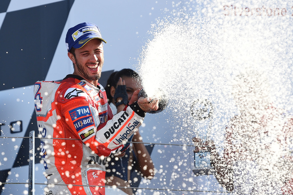Ducati Team's Italian rider Andrea Dovizioso celebrates first place on the rostrum after the MotoGP race of the British Grand Prix at Silverstone circuit in Northamptonshire, southern England, on August 27, 2017.