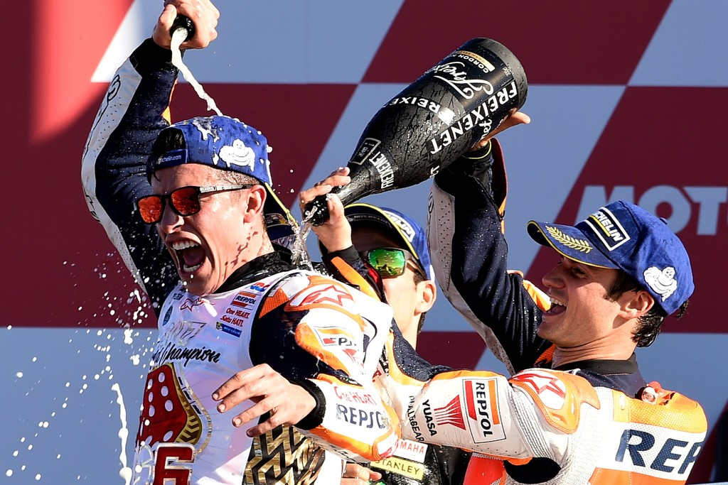 Repsol Honda Team's Spanish rider Dani Pedrosa (R) and Monster Yamaha Tech 3's French rider Johann Zarco spray cava on Repsol Honda Team's Spanish rider Marc Marquez (L) on the podium of the MotoGP race of the Valencia Grand Prix at Ricardo Tormo racetrack in Cheste, near Valencia on November 12, 2017. .Spain's Marc Marquez sealed his sixth world championship and fourth in the premier MotoGP category with third place at the Valencia Grand Prix. Marquez's Honda teammate Dani Pedrosa won the race from France's Johann Zarco in second.