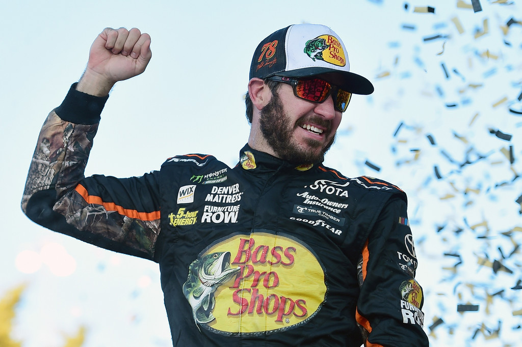 Martin Truex Jr., driver of the #78 Bass Pro Shops/Tracker Boats Toyota, celebrates in Victory Lane after winning the Monster Energy NASCAR Cup Series Hollywood Casino 400 at Kansas Speedway on October 22, 2017 in Kansas City, Kansas.